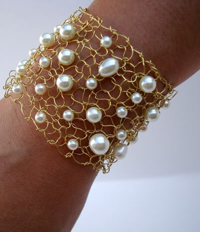 A brass knitted mesh bracelet with beads wears on somebody's wrist.