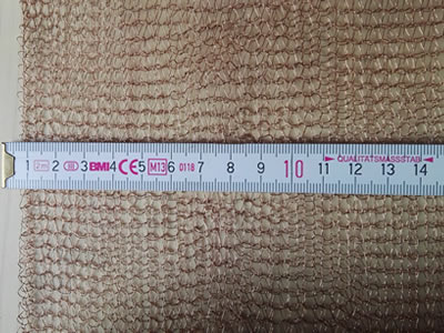 A metal ruler is measuring the width of knitted wire mesh and ruler displays the width is 16 cm.