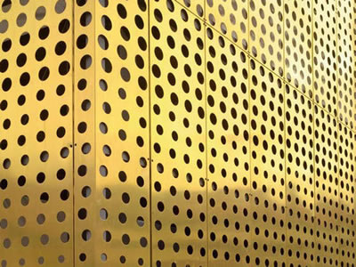 The picture shows brass perforated mesh facade with different sizes round.