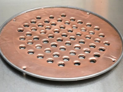 The picture shows a round copper perforated mesh with aluminum edge.