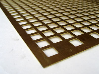 The picture shows a piece of square brass perforated mesh.