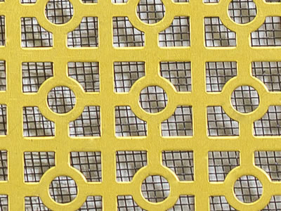 The picture shows a piece of square plus circle brass perforated mesh with the background of low carbon steel woven mesh.