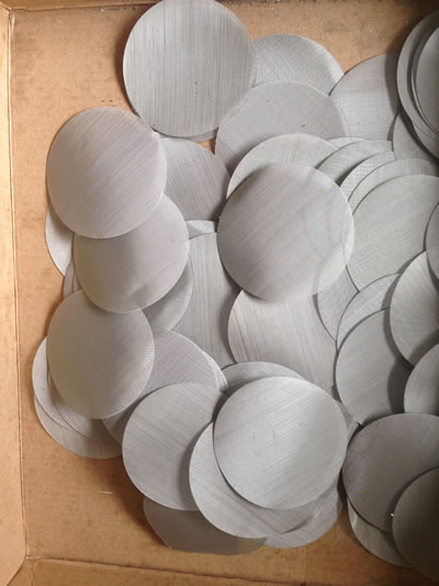 Many stainless steel mesh filter discs in a paper carton.